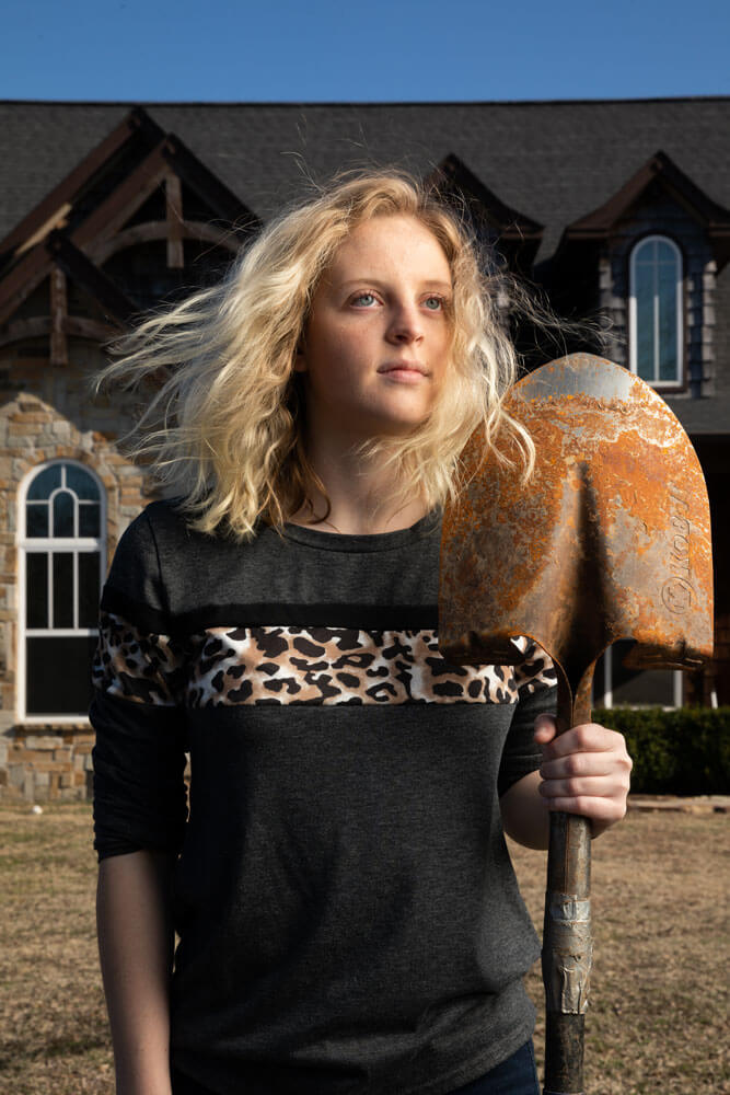 Kendall Hays holding a shovel in an 'American Gothic' inspired pose.
