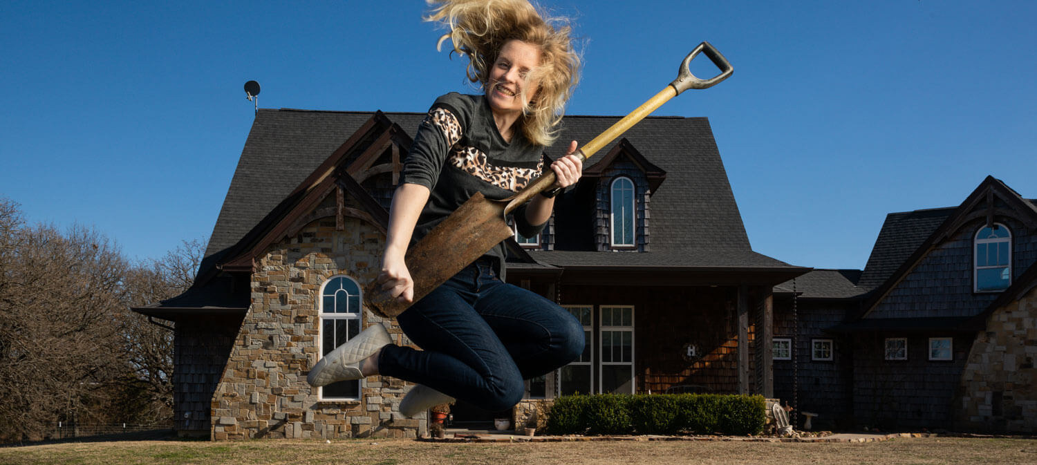 Kendall Hays jumps in mid-air with shovel.